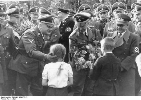 Kinder begrüßen Heinrich Himmler u. a.